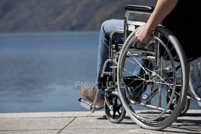 Cropped view of man in wheelchair sitting by water — Stock Photo