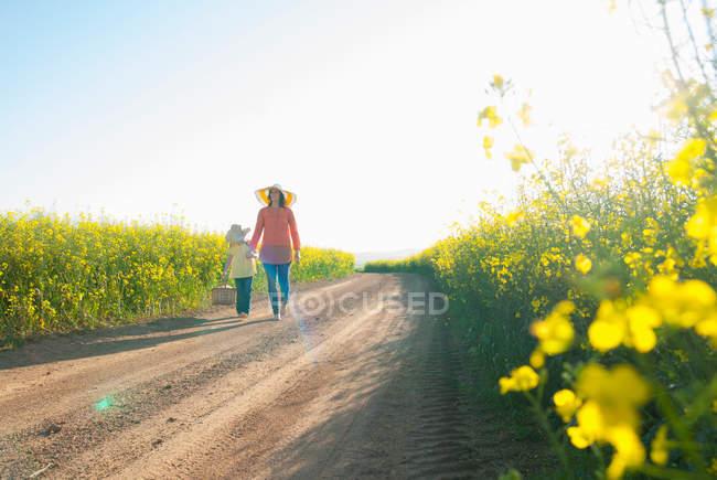 Мати і дочка ходіння по грунтовій дорозі — стокове фото