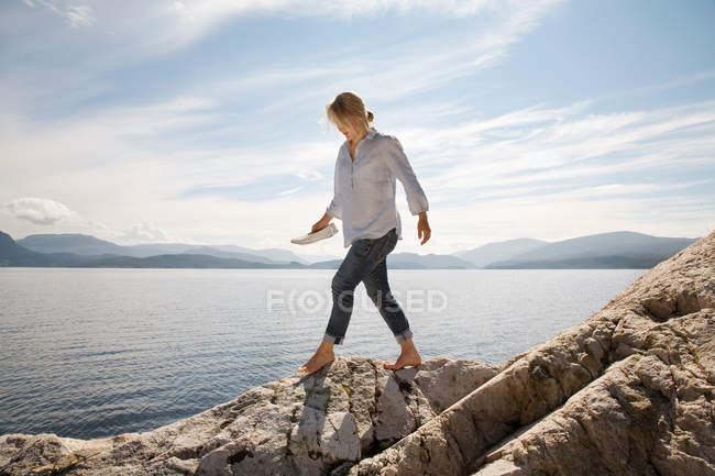 Mulher andando na praia rochosa por mar — Fotografia de Stock