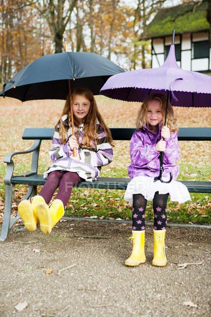 Filles en bottes de pluie et parasols dans le parc — Photo de stock