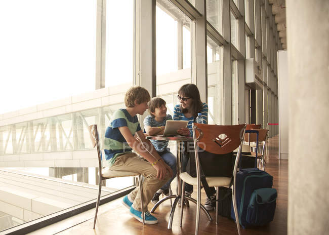 Mother and sons waiting in departure lounge at airport — Stock Photo