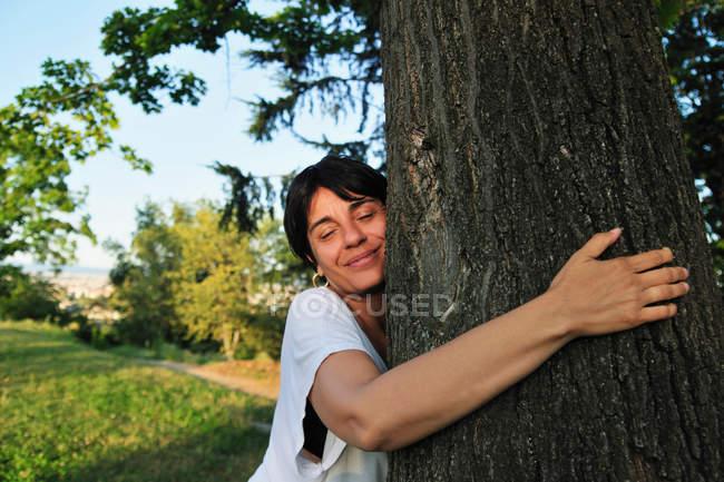 Donna che abbraccia albero nella foresta — Foto stock