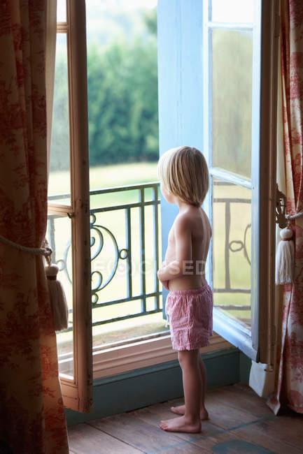 Мальчик смотрит в окно спальни — стоковое фото