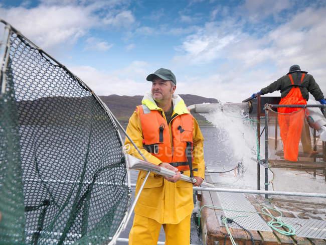 Man using large fishing net in Scottish salmon farm on loch — Stock Photo