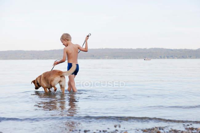Мальчик бродит с собакой на пляже — стоковое фото