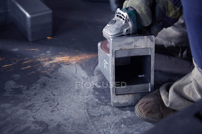 Person grinding in cast iron foundry — Stock Photo