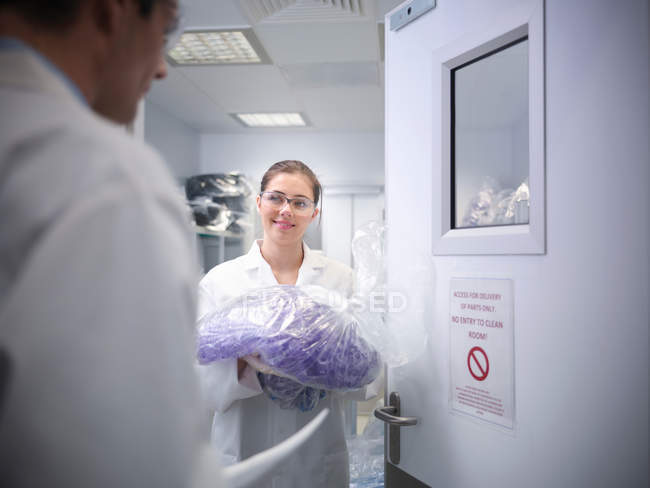 Female scientist holding plastic product outside clean room in laboratory, with male scientist in foreground — Stock Photo