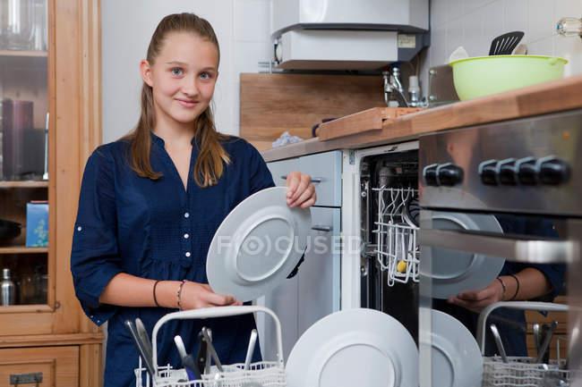 Smiling girl loading dishwasher, focus on foreground — Stock Photo