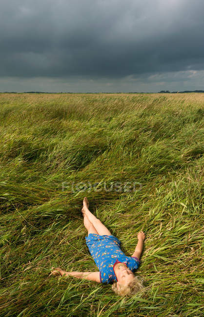 Girl relaxing in field of tall grass — Stock Photo