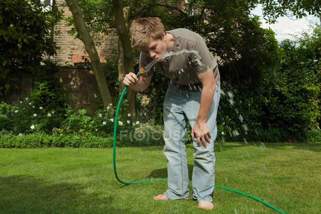Мальчик пьет воду из шланга на открытом воздухе — стоковое фото