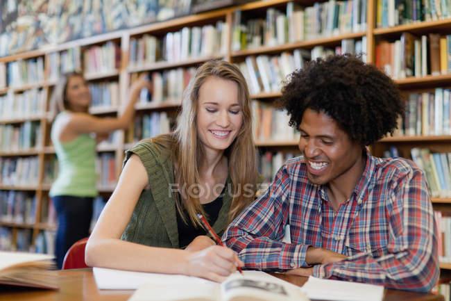 Étudiants étudiant ensemble à la bibliothèque — Photo de stock