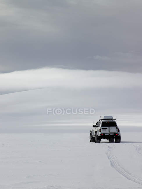 SUV driving on snow-covered glacier — Stock Photo