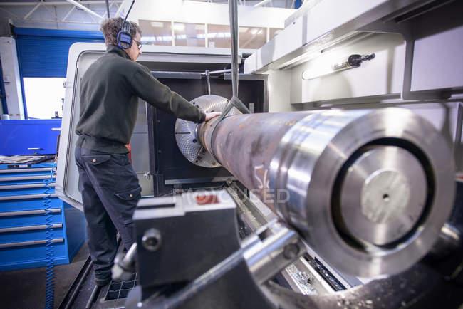 Ingenieur in Schutzbrille und Gehörschutz mit Kran, Stahl in Drehbank zu heben — Stockfoto