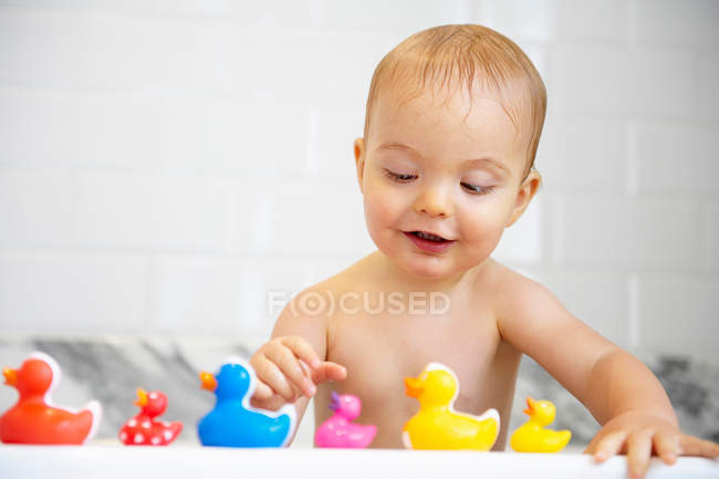 Boy playing with plastic ducks in bath — Stock Photo