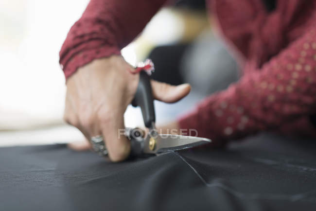 Seamstress hands using scissors to cut textile — Stock Photo