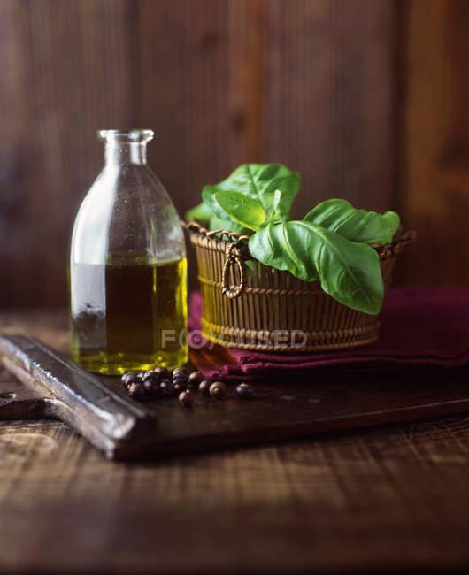 L'huile d'olive extra vierge, basilic et genièvre baies sur planche à découper en bois — Photo de stock