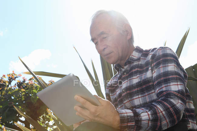 Older man using tablet computer outdoors — Stock Photo