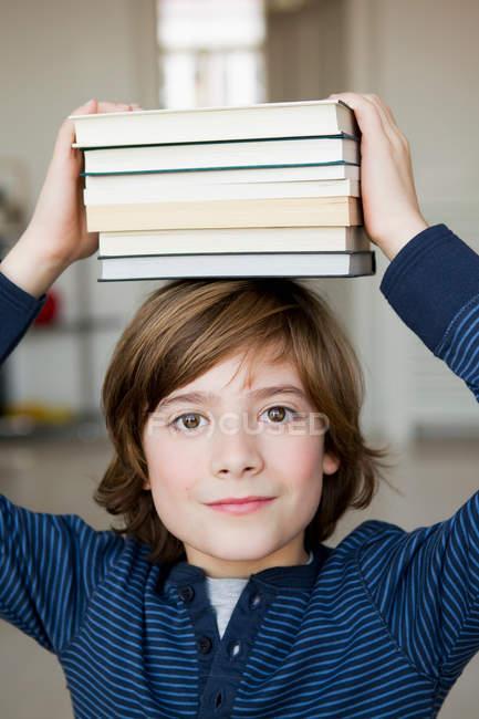 Ragazzo bilanciamento libri sulla testa, concentrarsi sul primo piano — Foto stock
