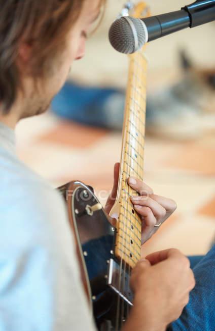 Человек играть на гитаре и петь — стоковое фото