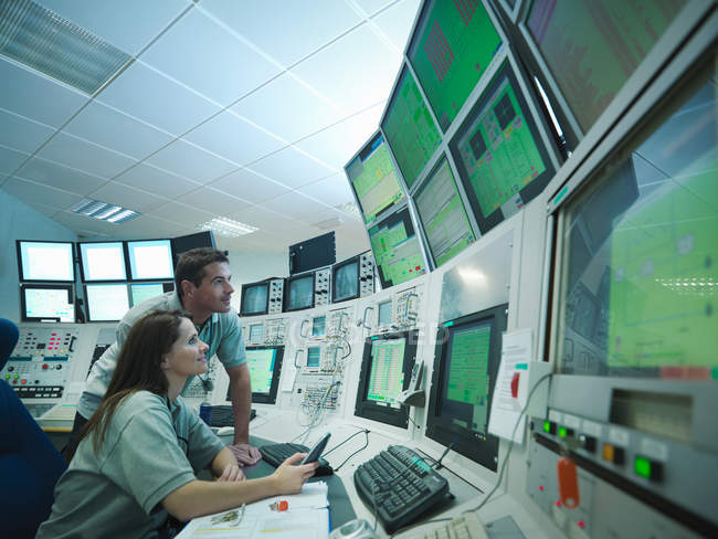 Cientistas na sala de controlo do acelerador de partículas, a olhar para monitores — Fotografia de Stock