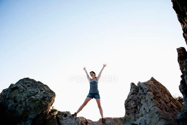 Femme acclamant sur les rochers contre le ciel bleu — Photo de stock