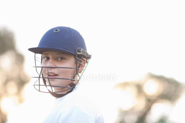Мальчик в крикетном шлеме смотрит в камеру — стоковое фото