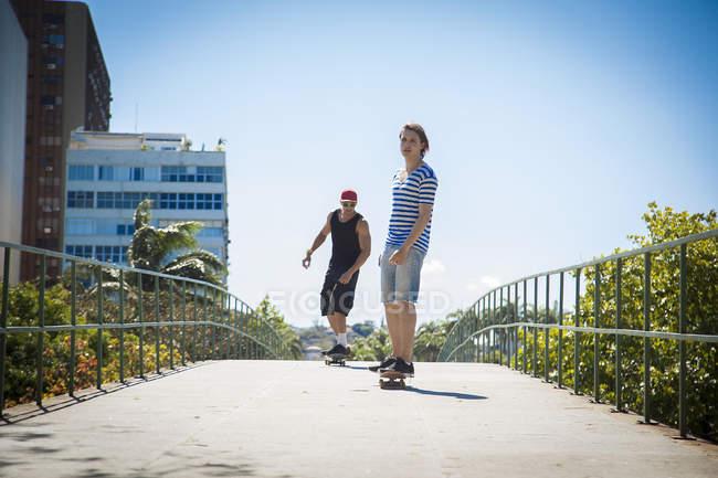 Двое мужчин, скейтбординг вдоль тротуара, низкий угол зрения — стоковое фото