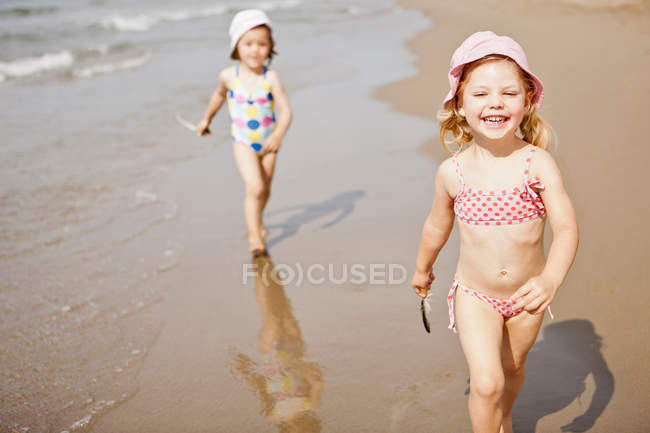Smiling girls walking in waves on beach — Stock Photo