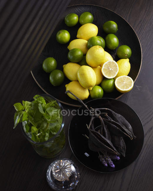 Lemons and limes in bowl — Stock Photo