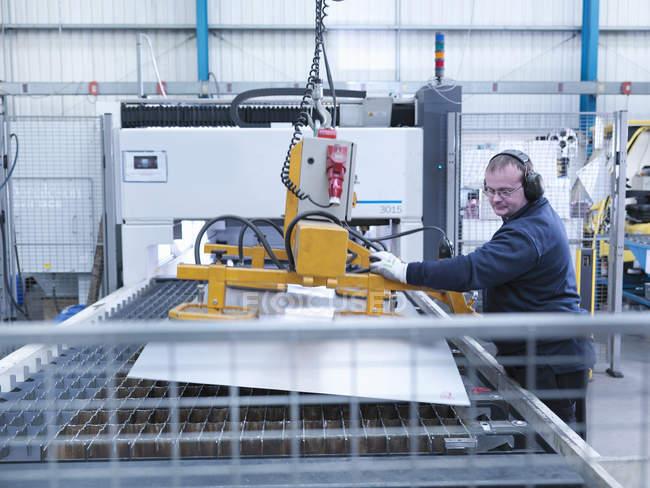 Ingenieur verlädt Blech in Laserschneidmaschine in Maschinenfabrik — Stockfoto