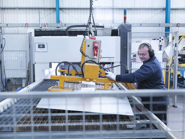 Engineer loading sheet metal into laser cutter in engineering factory — Photo de stock