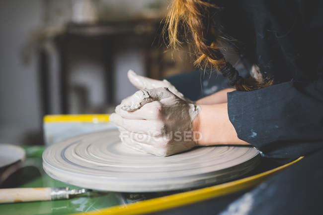 Боковой вид женских рук, образующих глину на гончарном круге — стоковое фото