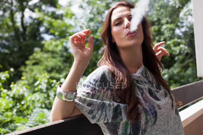 Donna che fuma sul balcone all'aperto — Foto stock