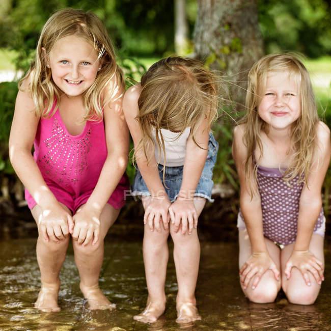 Lächelnde Mädchen, die im See spielen, Fokus auf den Vordergrund — Stockfoto