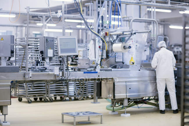 Rear view of factory worker operating food production machinery — Stock Photo