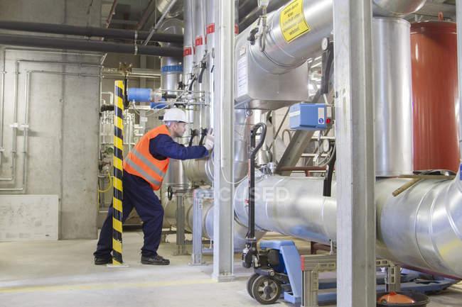 Технік, спираючись вперед під час перевірки на електростанції — стокове фото