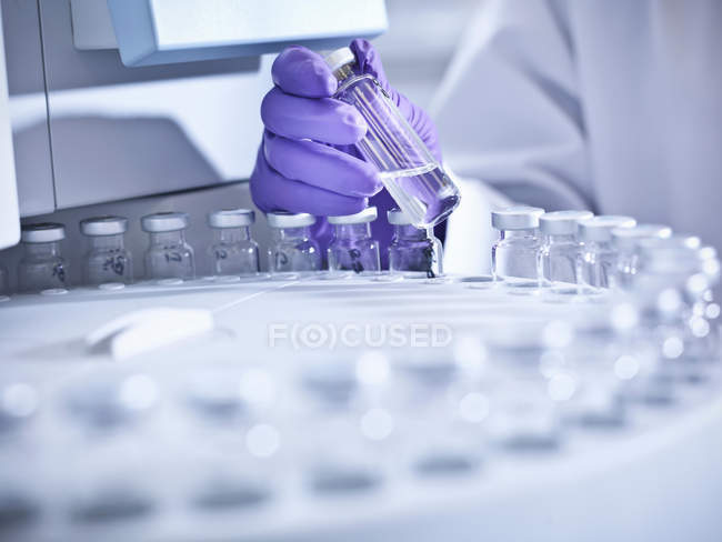 Scientist holding sample in laboratory with analytical scientific equipment — Stock Photo