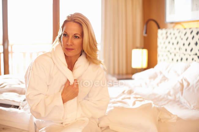 Femme portant un peignoir sur le lit — Photo de stock