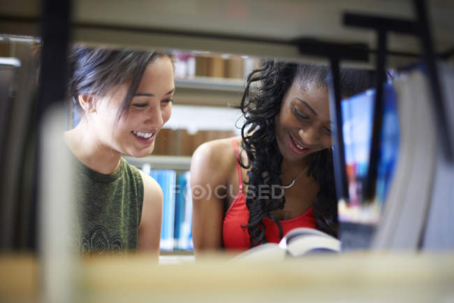 Two young female college students reading book on library shelves — Stock Photo