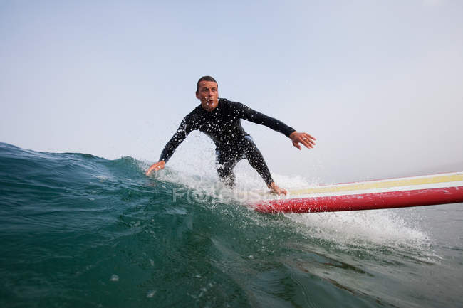 Man in swimming costume surfing a ocean wave, boobys bay, cornwall, england — Stock Photo