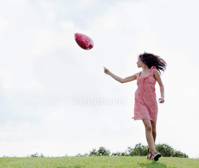 Teenager carrying heart shaped balloon — Stock Photo