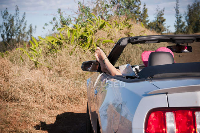Woman relaxing in convertible on road — Stock Photo