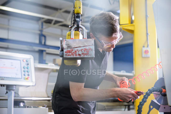 Engineer using tool to clean components in engineering factory — Stock Photo