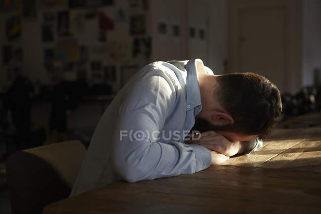 Joven sentado en la mesa de la cocina con la cabeza baja - foto de stock