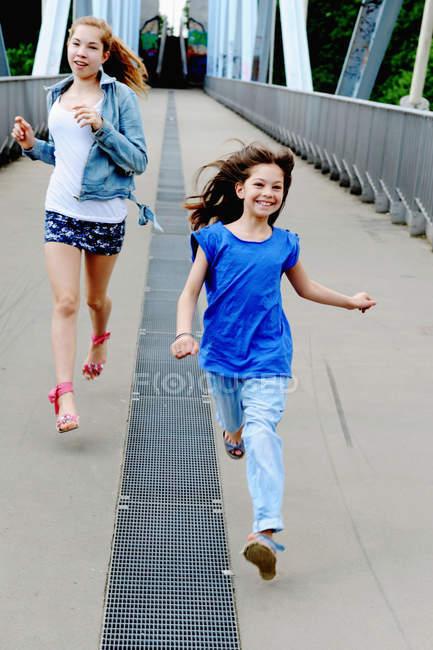 Ragazze che corrono sul ponte insieme — Foto stock