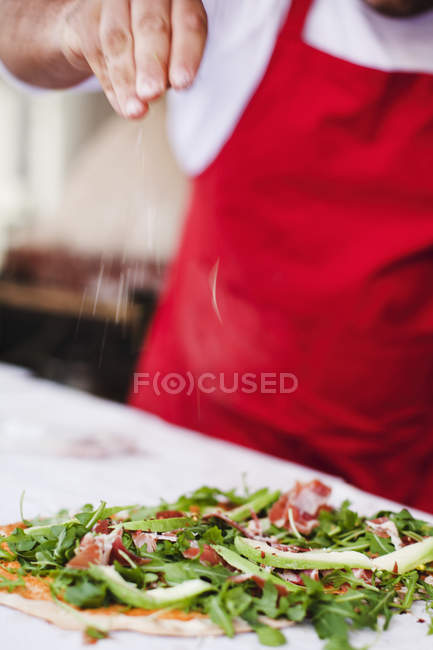 Chef sprinkling spices over pizza — Stock Photo