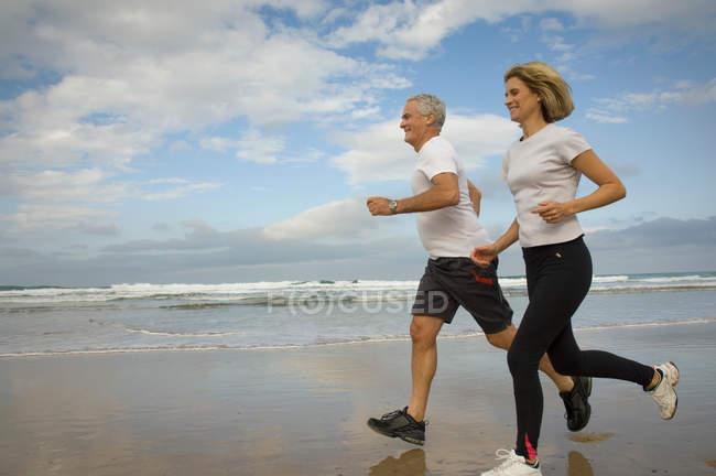 Couple running on a beach — Stock Photo