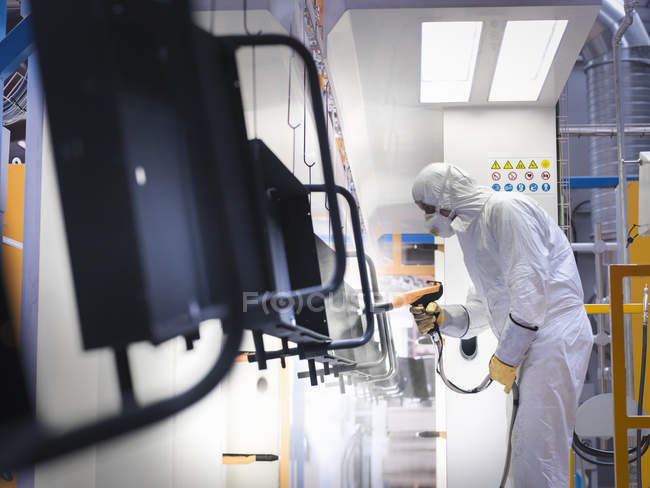 Trabalhador peças de revestimento em pó na cabine de pulverização de tinta na fábrica de chapas metálicas — Fotografia de Stock