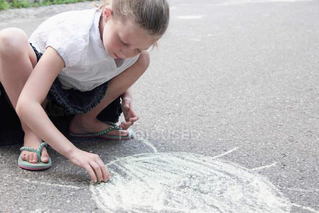 Girl drawing sun on sidewalk in chalk — Stock Photo