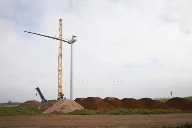 Wind turbine ériger avec grue dans le paysage industriel — Photo de stock
